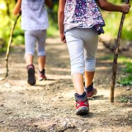 Children hiking in mountains or forest with sport hiking shoes. Girls are walking trough forest path wearing mountain boots and walking sticks. Frog perspective with focus on the shoes; blog: 10 Summer Outdoor Activities for Kids