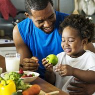 Dad and son cooking together; blog: 6 Ways to Help Your Child With Weight Management
