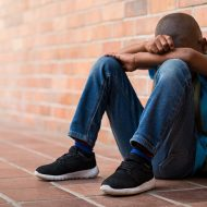Young boy sitting alone with sad feeling at school. Depressed african child abandoned in a corridor and leaning against brick wall. Bullying, discrimination and racism concept at school with copy space; blog: 20 Signs of Bullying