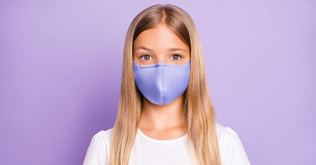 Close up photo of pretty positive cheerful child look have covid-19 quarantine her family, friends wear white breathing mask t-shirt clothes isolated over violet color background; blog: 5 Face Mask Facts for Kids