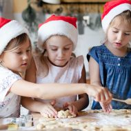 Children are cooking Christmas cookies in cozy home kitchen. Cute kids in santa hats preparation holiday dinner for family. Three sisters bake Xmas biscuits. Lifestyle moments. Children chef concept; blog: holiday safety tips for families