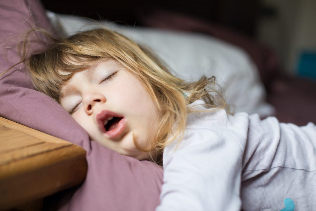 funny face expression with open mouth of blonde caucasian three years old child, sleeping on king bed; blog: Healthy Sleep Habits for Your Child