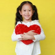 Portrait of happy asian little child girl cuddle a fluffy red heart with looking camera isolated on yellow background; blog: Heart-Healthy Activities for Kids
